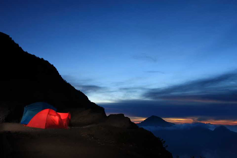 Camping in red tent pitched on Mt. Rinjani at sunset.