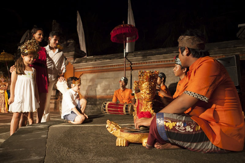 Club Med tourists enjoying local Indonesia musicians as they perform in front of temple.