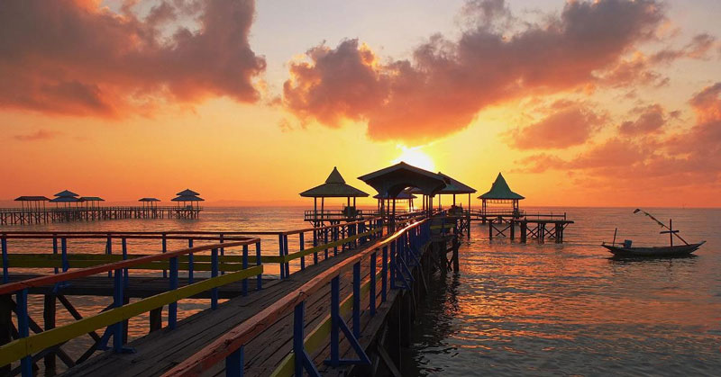 Hala Tourism promotional photo showing beustiful crimson sunset over a Lombok waterfront pier.